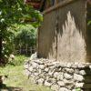 Eine Trockenmauer stützt das Haus in HanglageUna platea artificiale con muri a secco compensa la pendenzaA terrace set up with dry wall construction2710 BCVillanders-Plunacker, I